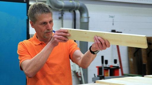 Ulf Hogräfer beim Zuschneiden von Holzbrettern
