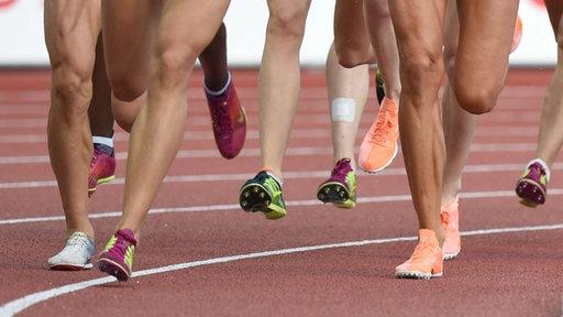 Füße von Läuferinnen auf Laufbahn