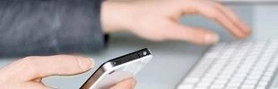 Zwei Hände - die eine hält ein Handy. Zusätzlich ist eine Tastatur zu sehen.