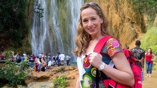 Tamina Kallert an einem Wasserfall, vor dem viele Touristen stehen