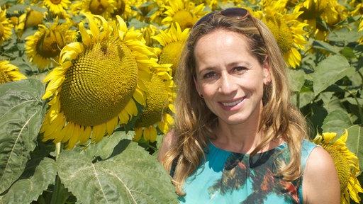 Moderatorin Tamina Kallert vor gelben Sonnenblumen