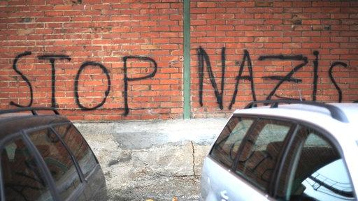 Schrift auf einer Mauer: Stop Nazis