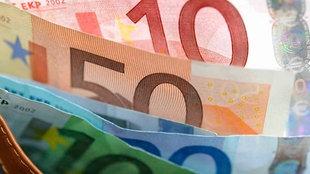 ein 500-Euro-Schein wird von einer Hand zu einer anderen gereicht