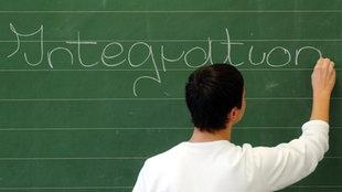 """Ein Schüler schreibt das Wort """"Integration"""" auf eine Tafel"""