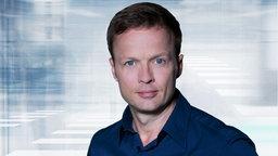 Georg Restle vor dem Logo der Sendung Monitor