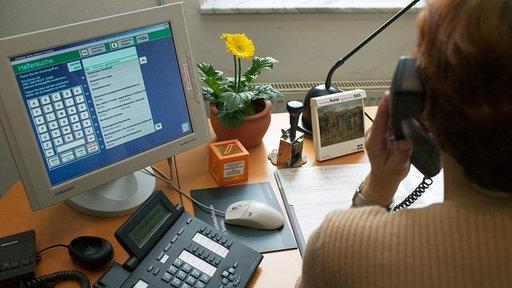 Frau am Schreibtisch mit Computermonitor