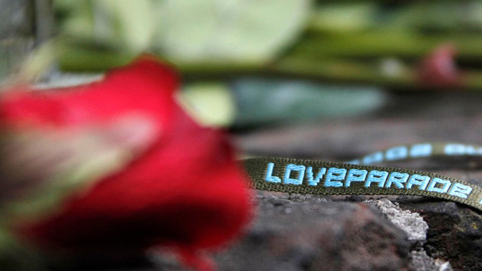 """Eine rote Rose und ein Stoffband mit der Aufschrift """"Loveparade"""""""