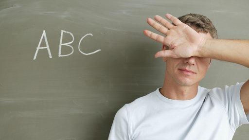 Ein Mann steht vor einer Tafel, auf der ABC geschrieben steht, und hält sich die Augen zu.