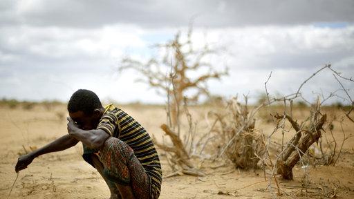 Ein Afrikaner sitzt auf vertrocknetem Boden.