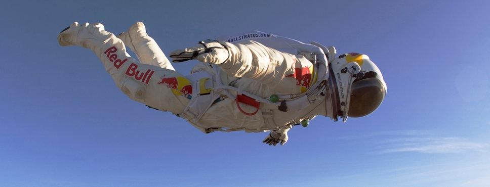 Aufnahme eines Extremsportlers im Astronautenanzug, der zu Schweben scheint, aber am Fallen ist.