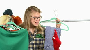 Socken-Handpuppe und Mädchen mit Kleidungsstücken