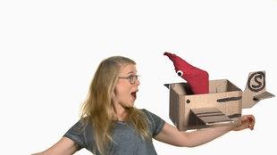 Socken-Handpuppe in einem Karton und Mädchen
