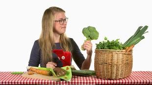 Socken-Handpuppe und Mädchen mit Gemüsekorb