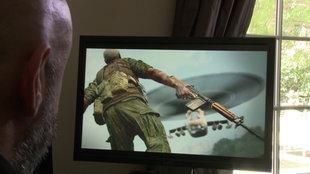 Ein Mann sitzt vor einem Computerbildschirm, auf dem ein Soldat mit Waffe geht