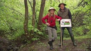 """Esther und André im Wald mit einem Schild mit der Aufschrift """"2 durch NRW"""""""