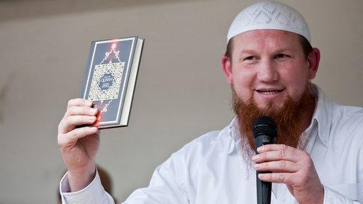 Pierre Vogel als Redner mit Mikrofon und einem Koran in der Hand bei einer salafistischen Verkündigungsveranstaltung.