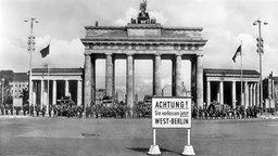 """Schwarzweiß-Bild: Brandenburger Tor mit Schild """"Achtung! Sie verlassen jetzt West-Berlin"""" davor."""
