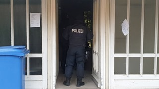 Polizist steht in Hauseingang