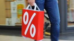 Eine Frau geht am 23.07.2012 mit einer Papiertüte, auf der ein großes Prozentzeichen zu sehen ist, durch ein Einkaufszentrum in Hamburg.