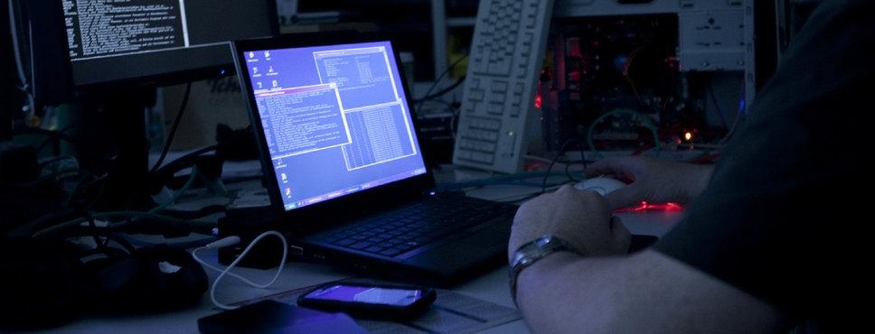 Ein Mann sitzt in einem abgedunkelten Raum vor verschiedenen Computern und Monitoren