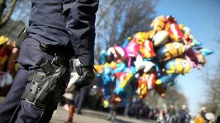 Archivbild: Ein mit einer Pistole bewaffneter Polizeibeamter  während des Rosenmontagszuges