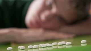 Antidepressiva: Ein junger Mann schaut auf Pillen, die vor ihm liegen.