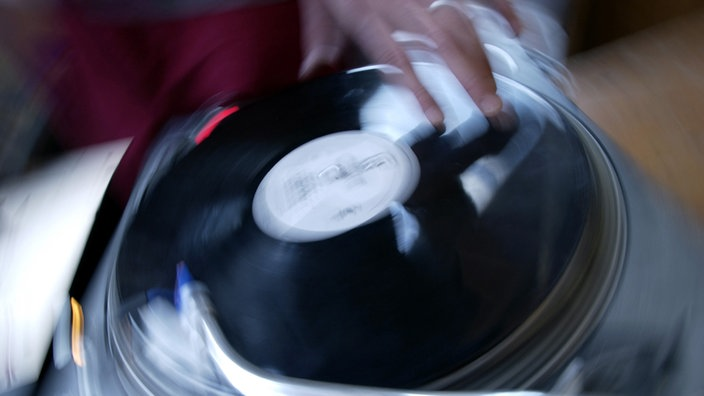 Ein Plattenspieler wird bei einer Hip Hop Veranstaltung durch einen DJ beim Scratching stark in Anspruch genommen