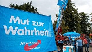 Passanten stehen am 01.09.2016 in Schwerin (Mecklenburg-Vorpommern) bei der Kundgebung zum Abschluss des AfD-Wahlkampfs in Mecklenburg-Vorpommern an einem Infostand der AfD