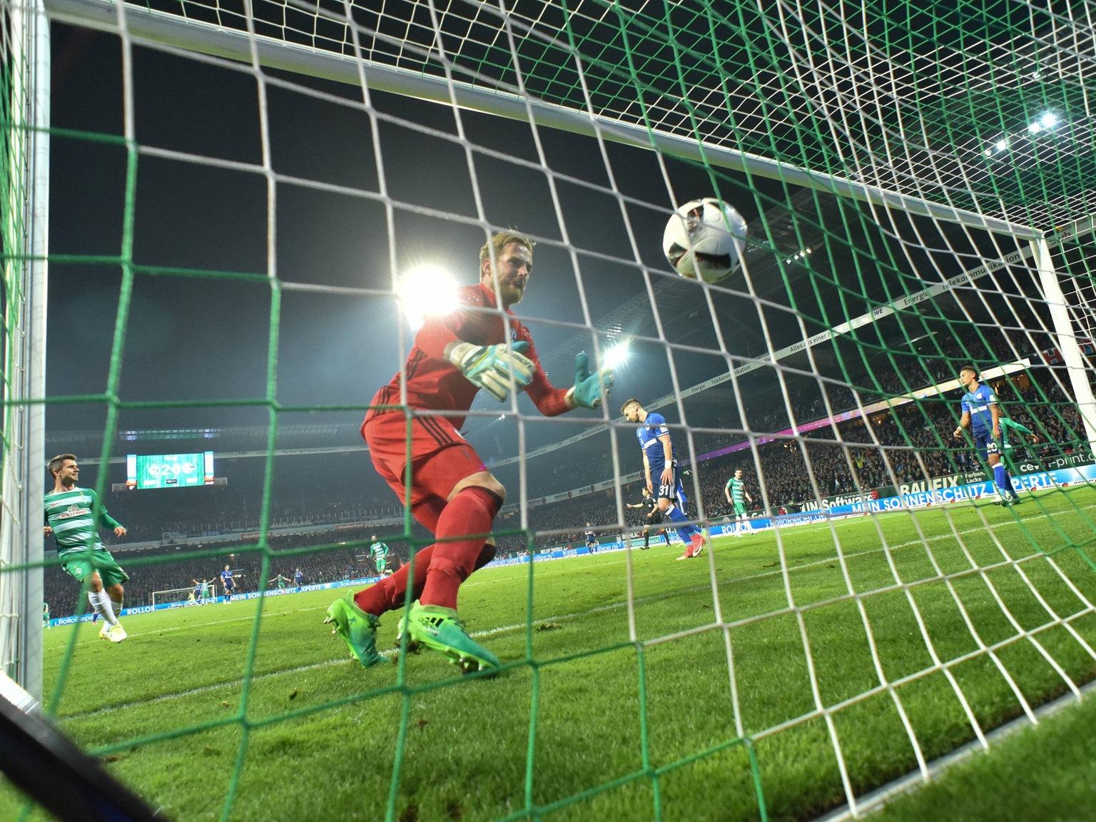 Ein Torwart greift hinter sich, um den Ball aus dem Netz zu holen