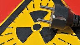 Ein Stromstecker vor einem Radioaktivitätszeichen