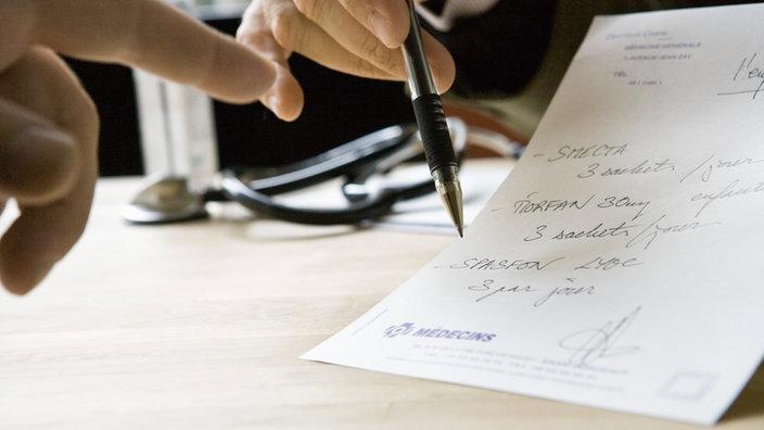Arzt erklärt Patient ein handschriftliches Rezept