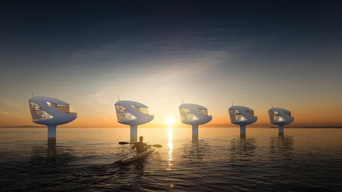 Sogenannte Seapods: Kleine Wohneinheiten auf Pfeilern in ruhigem Wasser, in deren Hintergrund die Sonne untergeht