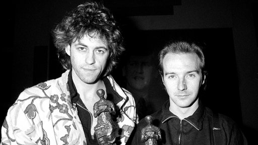 "Bob Geldorf (r.) und Midge Ure (l.) mit den Ivor Novello Award für ihre Benefiz-Single ""Do They Know It's Christmas"" (1984)"