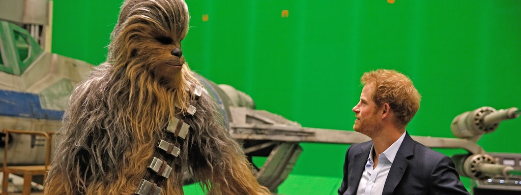 Britain's Prince Harry (R) meets Chewbacca during a visit to the Star Wars film set at Pinewood Studios