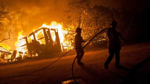 November 9, 2018 - Malibu, California - Firefighters walk along a structure fire during the Woolsey Fire in Malibu, California