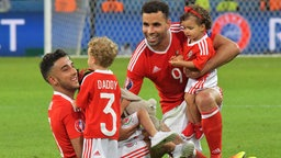 Neil Taylor (L) and Hal Robson-Kanu of Wales play on the pitch with their children after winning the UEFA EURO 2016 quarter final soccer match between Wales and Belgium at Stade Pierre Mauroy in Lille Metropole, France