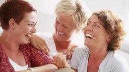 Frauen sitzen gesellig beieiander und lachen