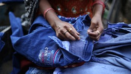 """Eine Frau näht an einer Jeans mit der Aufschrift """"If you can catch me"""" in dem Slum Shastri Park am Fluß Yamuna im Osten von Delhi, Indien"""