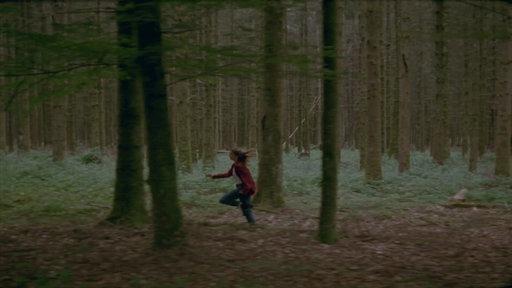 Ein Mädchen rennt durch den Wald.