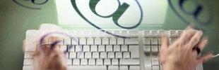 Eine Frau schreibt auf der Tastatur eines Computers, @ Symbole