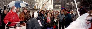 """Mehrere als Tod und Sensenmann verkleidete Menschen begleiten am 11.02.1991 auf dem Kölner Domplatz einen """"Verwundeten"""" in einem Krankenbett"""