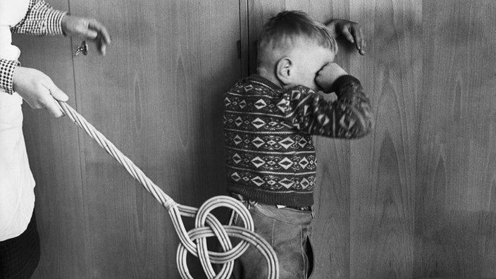 Frau schlägt Kind mit Teppichklopfer (gestelltes Foto aus den 1950er Jahren)