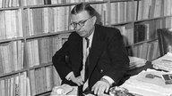 Schriftsteller und Philosoph Jean-Paul Sartre sitzt 1964 vor einem Bücherregal