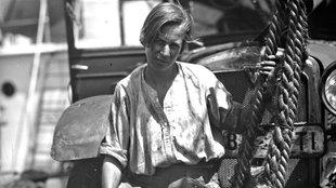 Clärenore Stinnes mit beschmutztem Hemd vor ihrem Auto