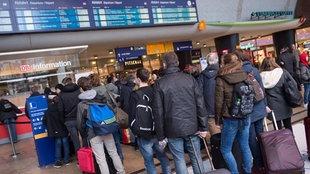 Reisende stehen am Hauptbahnhof in Köln