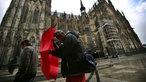 im Sturm gebeugt gehende Menschen am Kölner Dom