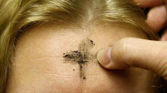 Ein Aschenkreuz bekommt eine Katholikin auf die Stirn gemalt.
