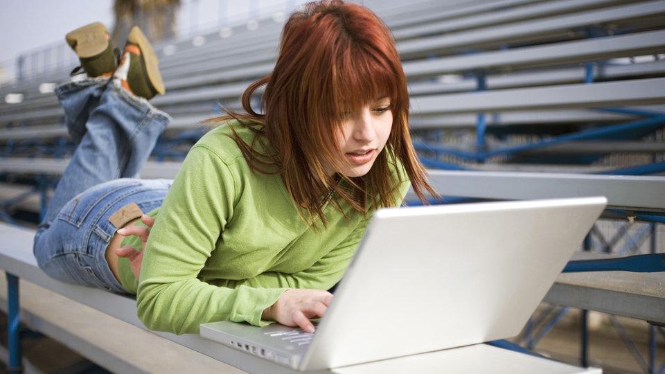 Junge Frau benutzt Notebook unterwegs