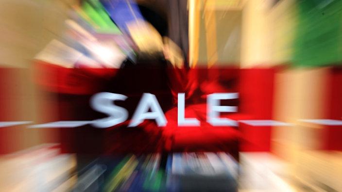 """Verschwommene Szene beim Einkaufen mit """"Sale""""-Schild"""