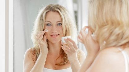 Frau steht vor dem Spiegel und cremt sich ein
